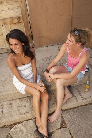 Two young women sitting on an outside porch and talking while enjoying a drink