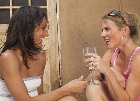 Dos mujeres j�venes sentados en un porche exterior y hablando mientras que goza de una bebida