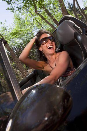 Una mujer joven y atractiva en conducir una descapotable de gafas de sol