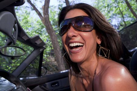 An attractive young woman in sunglasses driving a convertible Stock Photo