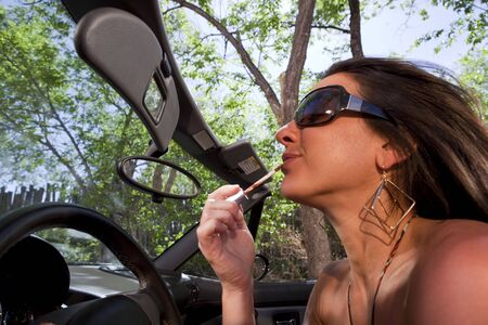 An attractive woman in a converitble applying lipstick in the rear view mirror while driving