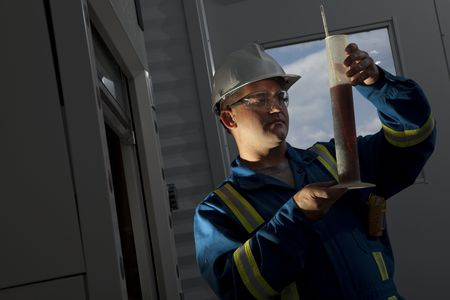 a petroleum worker looking at a liquid test in a column