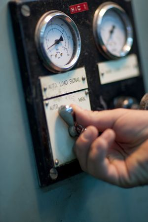The hand of an operator working controls in an industrial factory