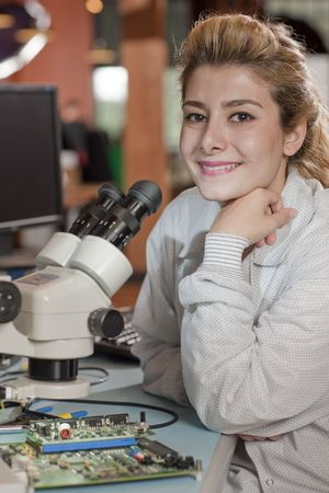An attractive young researcher sits at a desk with a microscope used to look at electronics. She is smiling towards the camera. Vertical shot. photo