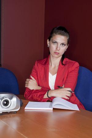 Empresaria joven atractiva en una chaqueta roja se sienta con los brazos cruzados y viste una expresi�n seria en su rostro. Un disparo vertical.