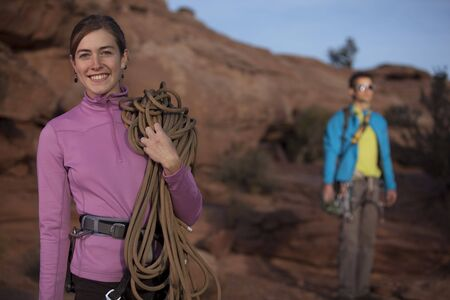An attractive young woman is smiling and holding a climbing rope as her partner stands in the background. Horizontal shot. Stock Photo