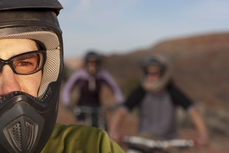 Closeup and cropped view of a male mountain biker in a helmet and protective eyewear. In the background are two other bikers. Horizontal shot. photo