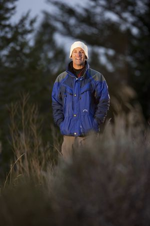 Portrait of a smiling man standing in a clearing in the wilderness. He is wearing a coat and hat. Vertical format. Stock Photo - 6781752
