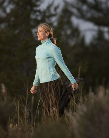 Side view of a woman standing and stretching in a clearing. She is smiling and looking off camera. Vertical format.