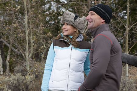 Side view of a couple in winter clothing, standing together by a fence in a wooded area. They are smiling and looking off into the distance. Horizontal format.