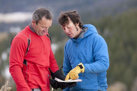 naar beneden kijken: Twee mannen staan en kijken neer op de kaart samen in de wildernis. Een man is wijzend op een plek op de kaart en praten. Horizontale indeling.