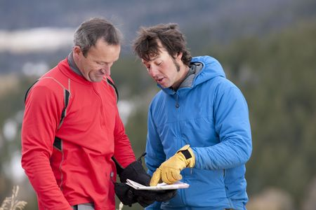 Two men stand and look down at a map together in the wilderness. One man is pointing at a spot on the map and talking. Horizontal format. photo