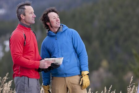 Two men stand together in a clearing in the wilderness and look out into the distance. One is holding a map. Horizontal format. Stock Photo