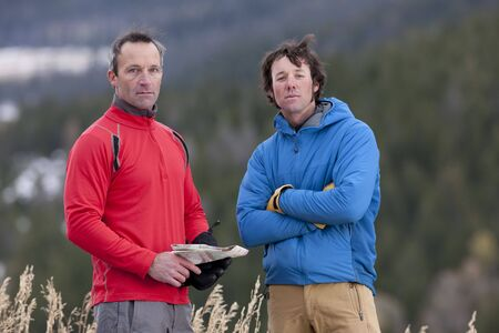 Two men stand together in the wilderness and look at the camera with serious expressions. One is holding a map. Horizontal format. Stock Photo