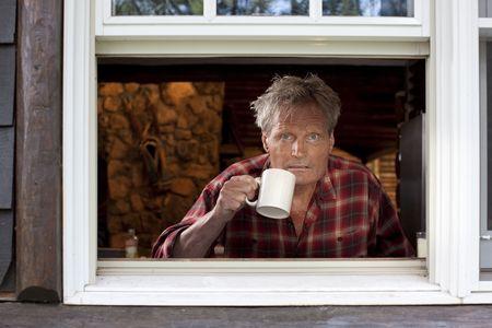 Retrato de un hombre de mediana edad con una camisa de plaid, mirando atentamente a una ventana abierta y la celebraci�n de una taza de caf�. La imagen es disparada desde fuera de la ventana, y �l est� mirando a la c�mara. Formato horizontal.