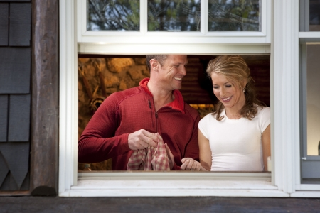 dishtowel: View from outside a window of a smiling couple doing dishes together in their kitchen. Horizontal format.