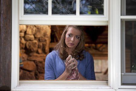 Portret van een schreeuwende vrouw staan op haar keuken raam en drogen van een schotel. Ze is gezien vanuit buiten het raam en staart in de verte als mascara over haar gezicht loopt. Horizontale indeling.  Stockfoto