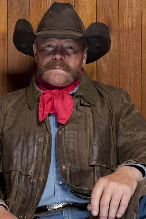 Portrait of a cowboy with a mustache in front of a rough wood wall. He is staring at the camera with a serious expression. Vertical format. Stock Photo