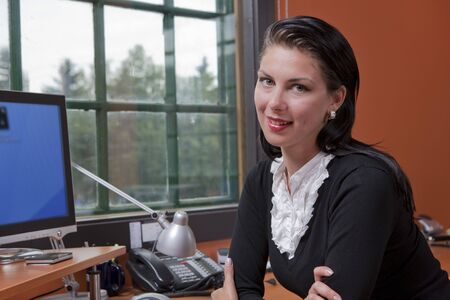 Portrait of a businesswoman sitting at a computer in her office. She is resting on her elbows and smiling at the camera. Horizontal format.
