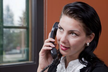 Close-up portrait of a businesswoman talking on the phone. She is looking up and off camera, and a window is visible behind her. photo