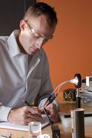 A researcher in a lab coat and goggles, making notes on an experiment. He is surrounded by scientific equipment. Vertical format. Stock Photo