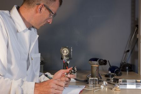 Cropped profile of a researcher in a lab coat and goggles, making notes on an experiment. He is surrounded by scientific equipment. Horizontal format. Stock Photo