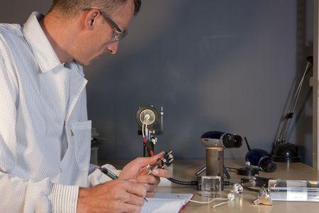 Recorta el perfil de un investigador en una bata de laboratorio y gafas protectoras, haciendo notas sobre un experimento. Est� rodeado de material cient�fico. Formato horizontal.