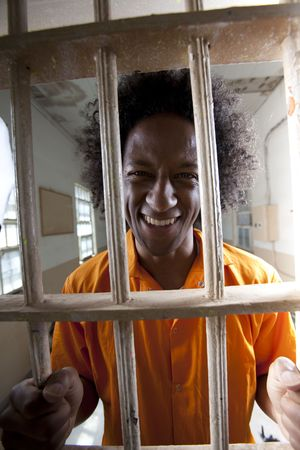 Portrait of a male prisoner with an orange jumpsuit and afro gripping the bars of a prison cell and smiling at the camera. Vertical format.