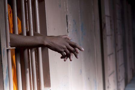 Recorta la vista de un preso en un traje de color naranja de pie en una celda de la prisi�n con los brazos extendidos a trav�s de las barras. Formato horizontal.  Foto de archivo