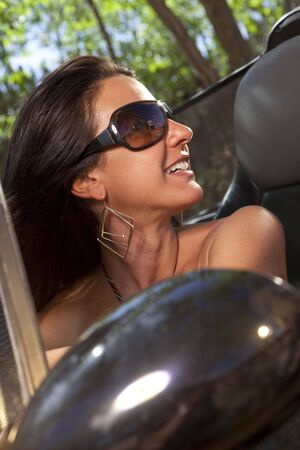Close-up tilt view of an attractive young woman in sunglasses driving a convertible. She is smiling and looking back over her shoulder. Vertical format. Stock Photo