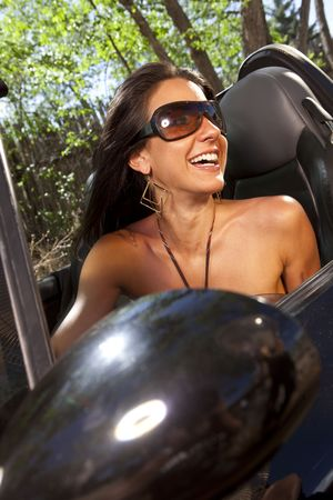 Tilt view of an attractive young woman in sunglasses driving a convertible. She is smiling and looking out the side of the car. Vertical format.
