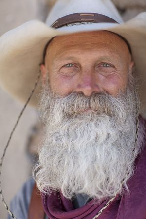 Portrait of an older man with a long white beard and cowboy hat smiling towards the camera. Vertical shot. photo