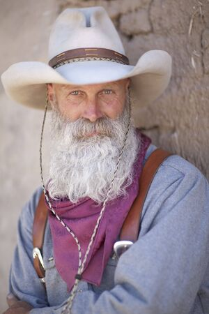 cowboy beard: Portrait of a cowboy wearing a tall hat and sporting a long white beard. He is dressed in a heavy work shirt and kerchief. Vertical shot. Stock Photo