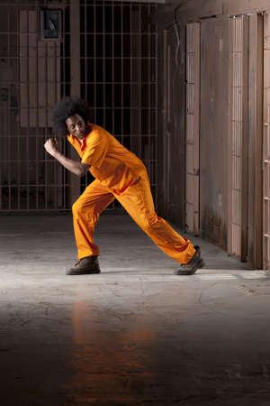Un joven africano americano con un afro es mirar detr�s de �l como �l est� haciendo un escape de una celda de la prisi�n. Un disparo vertical.