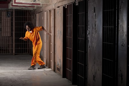 escape: A young african american man with an afro is sneaking out of a prison cell. Vertical shot.