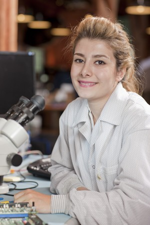 A attractive young female researcher in a lab coat is smiling as she sits in front of a microscope. Vertical shot. Stock Photo - 6965422