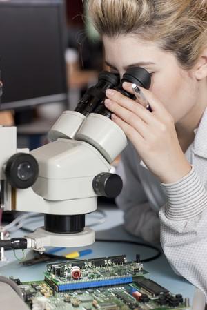 Un joven investigador femenino en una bata de laboratorio es peering en un microscopio. Un disparo vertical.