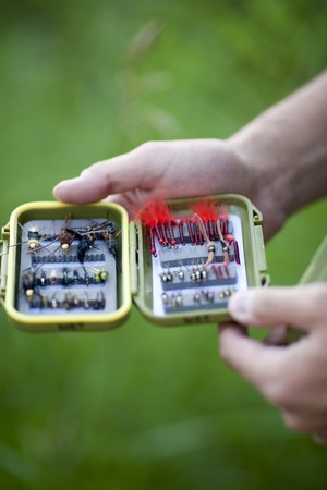 A pair of male hands is holding an open box of flies for fly fishing. Vertical shot. Stock Photo - 6987162
