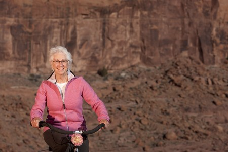 A senior woman is smiling as she rides her bike in a desert setting. Horizontal shot.