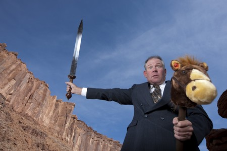 A businessman is holding a sword in an attack posture while riding a stick pony in a desert setting. Horizontal shot. Stock Photo - 6965405