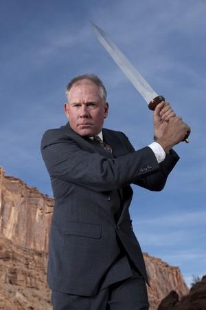 Un hombre de negocios est� celebrando una espada en una postura de ataque en una configuraci�n de desierta. Horizontal a tiros.