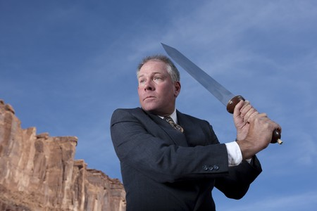 A businessman is holding a sword in an attack posture in a desert setting. Horizontal shot.