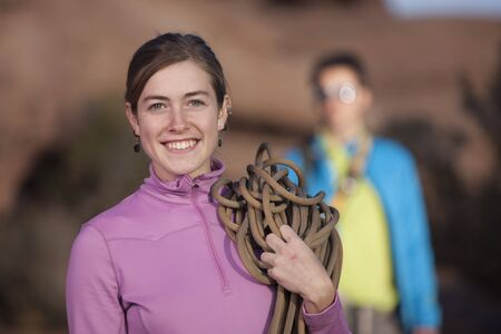 An attractive young woman is holding a rope used for mountain climbing. Her partner can be seen in the background. Vertical shot. Stock Photo