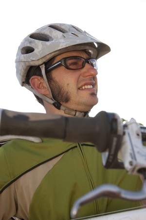 A young man wearing protective eyewear and a helmet is carrying a mountain bike. Vertical shot. Stock Photo