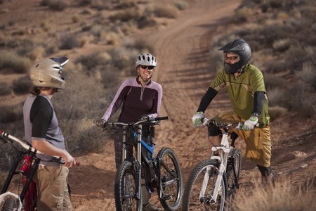 A group of mountain bikers is wearing protective eyewear and a helmets in a desert setting. Vertical shot. Stock Photo