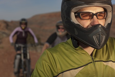 A group of mountain bikers is wearing protective eyewear and a helmets in a desert setting. Horizontal shot. Stock Photo