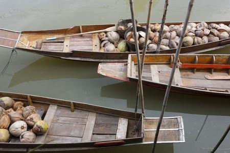 Barcos tradicionales en un mercado flotante son amarrados en un r�o. Est�n llenos de frutas cosechadas. Horizontal a tiros.