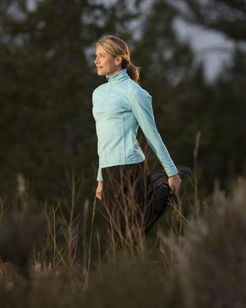 Una mujer joven atractiva es vistiendo ropa atl�tica y estiramiento antes de correr. Ella es sonriendo y frente al sol. Un disparo vertical.  Foto de archivo