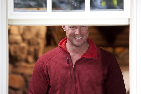 A man wearing a red shirt is smiling and looking out of a window. Horizontal shot. Stock Photo
