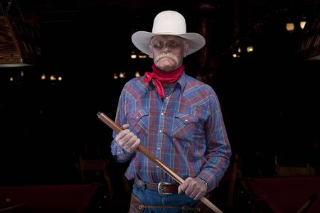 A senior man wearing a hat and western attire is standing in a darkened room holding a pool cue. He has an angry facial expression. Horizontal shot.